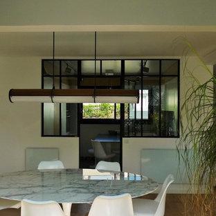 Неиссякаемый источник вдохновения для домашнего уюта: изолированная гостиная комната среднего размера в современном стиле с белыми стенами, полом из фанеры и коричневым полом без камина, ТВ