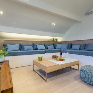 Réalisation d'une salle de séjour marine avec un mur blanc, un sol en bois clair, un téléviseur indépendant et un sol beige.