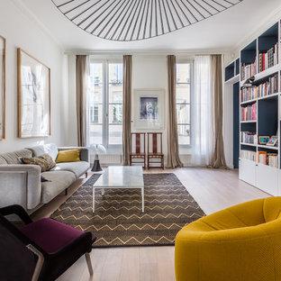 Aménagement d'une salle de séjour avec une bibliothèque ou un coin lecture contemporaine avec un mur blanc, un sol en bois clair, aucune cheminée et un téléviseur encastré.