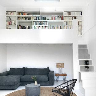 Aménagement d'une grande salle de séjour avec une bibliothèque ou un coin lecture contemporaine ouverte avec un mur blanc, un sol en bois peint, un sol blanc et aucun téléviseur.