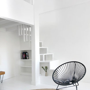 パリの大きいコンテンポラリースタイルのおしゃれなファミリールーム (ライブラリー、白い壁、塗装フローリング、標準型暖炉、レンガの暖炉まわり、白い床、テレビなし) の写真