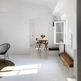パリの大きいコンテンポラリースタイルのおしゃれなオープンリビング (ライブラリー、白い壁、塗装フローリング、標準型暖炉、レンガの暖炉まわり、白い床、テレビなし) の写真