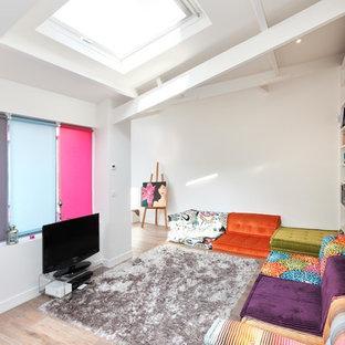 Cette image montre une salle de séjour avec une bibliothèque ou un coin lecture design de taille moyenne avec un mur blanc, un sol en bois brun, aucune cheminée et un téléviseur indépendant.
