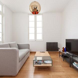 Inspiration pour une salle de séjour minimaliste de taille moyenne et fermée avec un mur blanc, un sol en bois brun et un téléviseur indépendant.