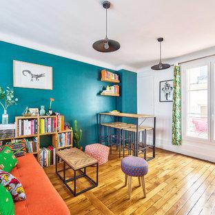 パリの中サイズのインダストリアルスタイルのおしゃれなファミリールーム (青い壁、淡色無垢フローリング、ベージュの床、ホームバー、壁掛け型テレビ) の写真