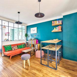 Esempio di un soggiorno bohémian di medie dimensioni e aperto con angolo bar, pareti verdi, pavimento in legno massello medio, nessun camino, TV a parete e pavimento marrone