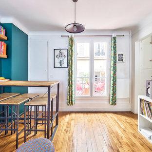 Ispirazione per un soggiorno minimalista di medie dimensioni e aperto con pareti blu, parquet chiaro, pavimento beige, sala della musica, nessun camino e TV a parete