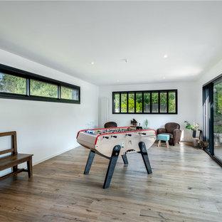 Idées déco pour une salle de séjour contemporaine fermée avec salle de jeu, un mur blanc, un sol en bois brun et un sol marron.