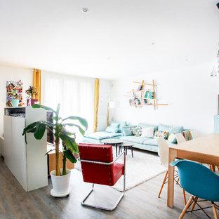 リヨンの広い北欧スタイルのおしゃれなオープンリビング (ライブラリー、白い壁、無垢フローリング、据え置き型テレビ、茶色い床) の写真