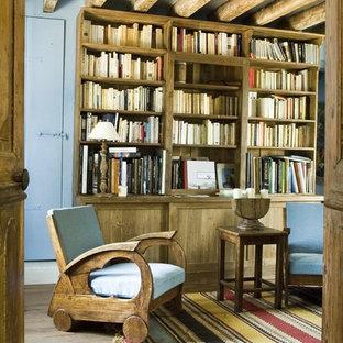 Idée de décoration pour une salle de séjour avec une bibliothèque ou un coin lecture chalet fermée et de taille moyenne avec un mur bleu, un sol en bois brun, aucune cheminée et aucun téléviseur.