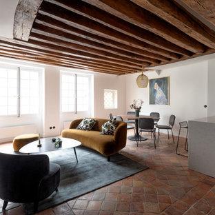 パリの中くらいのコンテンポラリースタイルのおしゃれなオープンリビング (白い壁、テラコッタタイルの床、標準型暖炉、タイルの暖炉まわり、内蔵型テレビ、赤い床) の写真