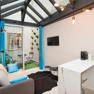 Cette photo montre une petite salle de séjour tendance ouverte avec un mur blanc, un sol en bois clair, un téléviseur fixé au mur et aucune cheminée.