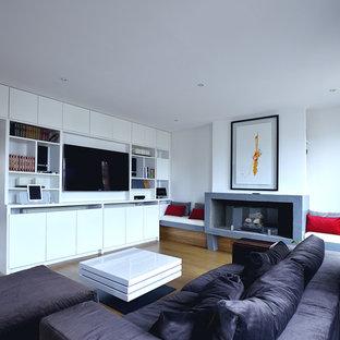 Foto de sala de estar con biblioteca abierta, contemporánea, de tamaño medio, con paredes blancas, suelo de madera clara, chimeneas suspendidas, marco de chimenea de hormigón, pared multimedia y suelo beige