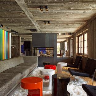 Aménagement d'une grand salle de séjour montagne ouverte avec une cheminée double-face, un manteau de cheminée en métal et aucun téléviseur.