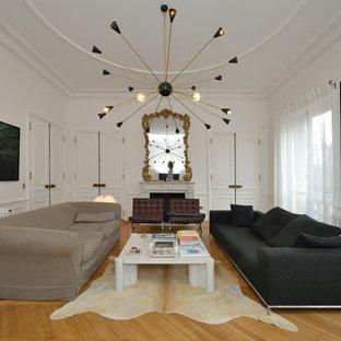 Aménagement d'une grande salle de séjour contemporaine fermée avec un mur blanc, un sol en bois clair, aucune cheminée et aucun téléviseur.