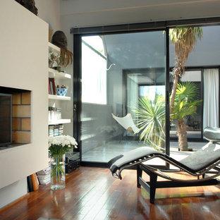Idées déco pour une salle de séjour contemporaine de taille moyenne avec un mur blanc, un sol en bois brun et une cheminée standard.