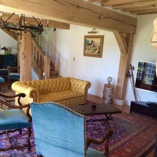 Foto de sala de estar abierta, de estilo de casa de campo, con paredes blancas, suelo de baldosas de terracota, chimenea tradicional, marco de chimenea de piedra, televisor independiente y suelo rojo