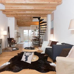 Cette image montre une salle de séjour design de taille moyenne et ouverte avec un mur blanc et un sol en bois brun.