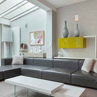 Réalisation d'une salle de séjour design avec un mur gris.