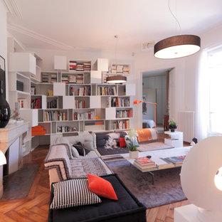 Cette image montre une salle de séjour avec une bibliothèque ou un coin lecture design de taille moyenne et fermée avec un mur blanc, un sol en bois brun, une cheminée standard, un manteau de cheminée en pierre et aucun téléviseur.