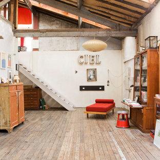 Inspiration pour une grande salle de séjour avec une bibliothèque ou un coin lecture urbaine fermée avec un mur blanc, un sol en bois brun et aucun téléviseur.