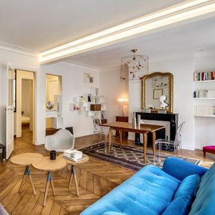 Cette image montre une grande salle de séjour avec une bibliothèque ou un coin lecture design ouverte avec un mur blanc, un sol en bois brun, une cheminée standard, un manteau de cheminée en pierre et un téléviseur indépendant.