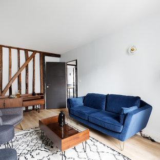 Idée de décoration pour une salle de séjour tradition fermée avec un mur blanc, un sol en bois clair et un sol beige.