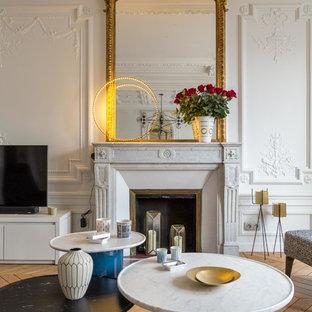 Réalisation d'une salle de séjour design de taille moyenne et fermée avec un mur blanc, un sol en bois brun, une cheminée standard, un manteau de cheminée en pierre et un téléviseur indépendant.