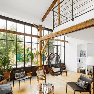 Immagine di un soggiorno industriale di medie dimensioni e aperto con pareti bianche, parquet chiaro, nessun camino e nessuna TV
