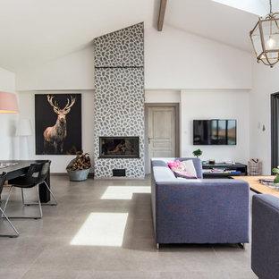 Idées déco pour une salle de séjour contemporaine ouverte avec un mur blanc, un sol en carrelage de céramique, une cheminée standard, un téléviseur fixé au mur, un sol gris et un manteau de cheminée en pierre.