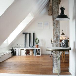 Exemple d'une salle de séjour avec une bibliothèque ou un coin lecture tendance de taille moyenne avec un mur blanc et un sol en bois brun.