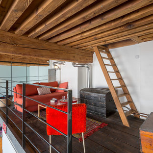 Idée de décoration pour une salle de séjour mansardée ou avec mezzanine urbaine avec un mur blanc, un sol en bois foncé, aucune cheminée, un téléviseur fixé au mur et un sol marron.