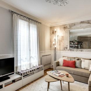 Idée de décoration pour une salle de séjour tradition avec un mur gris, un sol en bois brun et un téléviseur indépendant.