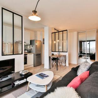 Foto de sala de estar abierta, urbana, de tamaño medio, con paredes blancas, suelo de madera clara y televisor independiente