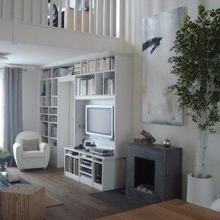 Aménagement d'une salle de séjour avec une bibliothèque ou un coin lecture contemporaine de taille moyenne et ouverte avec un mur blanc, un sol en bois brun, une cheminée standard et un téléviseur fixé au mur.