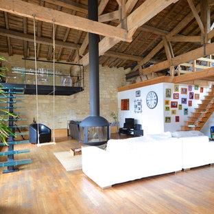Inspiration pour une salle de séjour urbaine ouverte avec un sol en bois brun, cheminée suspendue et un mur blanc.