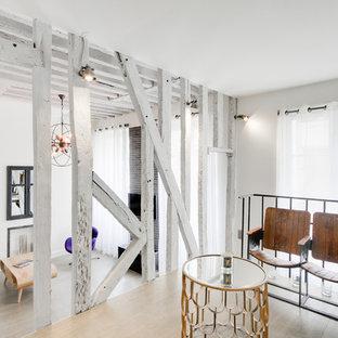 Cette image montre une salle de séjour mansardée ou avec mezzanine urbaine avec un mur blanc et un sol en bois clair.
