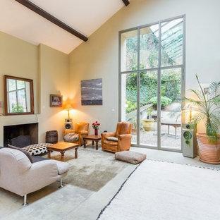 Idées déco pour une grand salle de séjour éclectique ouverte avec un mur beige, béton au sol, une cheminée standard et aucun téléviseur.