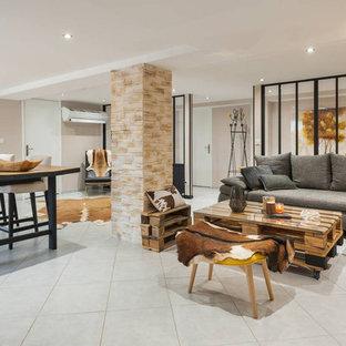 リヨンの大きいインダストリアルスタイルのおしゃれなファミリールーム (ベージュの壁、セラミックタイルの床、暖炉なし、据え置き型テレビ、白い床) の写真