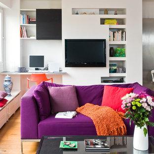 Cette photo montre une salle de séjour avec une bibliothèque ou un coin lecture éclectique ouverte et de taille moyenne avec un mur blanc, un sol en bois brun, aucune cheminée et un téléviseur fixé au mur.