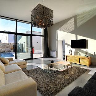 Cette image montre une grand salle de séjour design fermée avec un mur beige, un sol en carrelage de céramique et un téléviseur fixé au mur.
