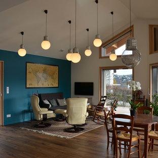 サンテティエンヌの大きいトランジショナルスタイルのおしゃれなファミリールーム (青い壁、無垢フローリング、薪ストーブ、壁掛け型テレビ、茶色い床) の写真
