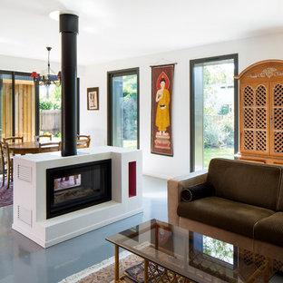 Modelo de sala de estar abierta, contemporánea, con paredes blancas, chimenea de doble cara y suelo gris