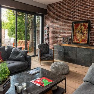 Cette image montre une salle de séjour bohème de taille moyenne et ouverte avec un mur rouge, un sol en bois brun et aucun téléviseur.