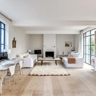 Réalisation d'une grande salle de séjour avec une bibliothèque ou un coin lecture design ouverte avec un mur blanc, un sol en bois clair, une cheminée standard, un téléviseur indépendant et un manteau de cheminée en plâtre.