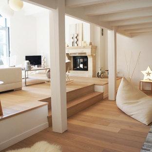 Inspiration pour une grand salle de séjour design ouverte avec un mur blanc, un sol en bois brun, une cheminée standard, un manteau de cheminée en pierre et un téléviseur indépendant.