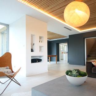 Aménagement d'une grande salle de séjour contemporaine ouverte avec un mur noir, béton au sol, aucune cheminée, aucun téléviseur et un sol gris.