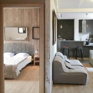 Ejemplo de sala de estar con barra de bar abierta, campestre, grande, sin chimenea, con paredes beige, suelo de madera clara, televisor en una esquina y suelo beige