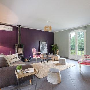 Imagen de sala de estar tradicional renovada con paredes púrpuras, suelo de baldosas de cerámica y estufa de leña