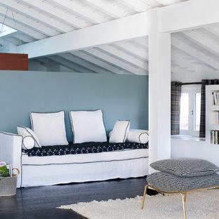 Cette image montre une salle de séjour avec une bibliothèque ou un coin lecture marine avec un mur bleu, un sol en bois foncé et aucune cheminée.
